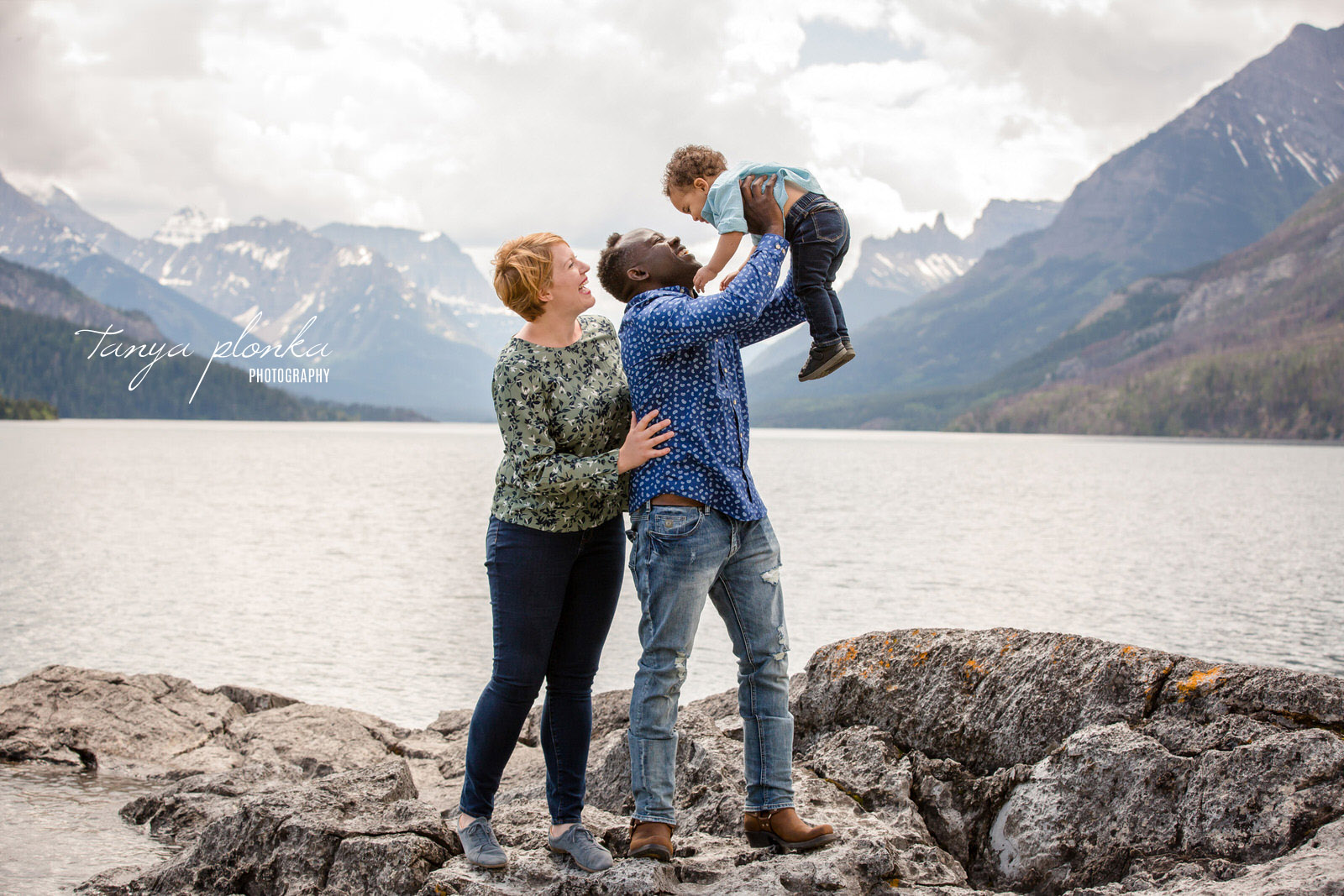 mom stands behind dad lifting toddler in front of lake and mountain view
