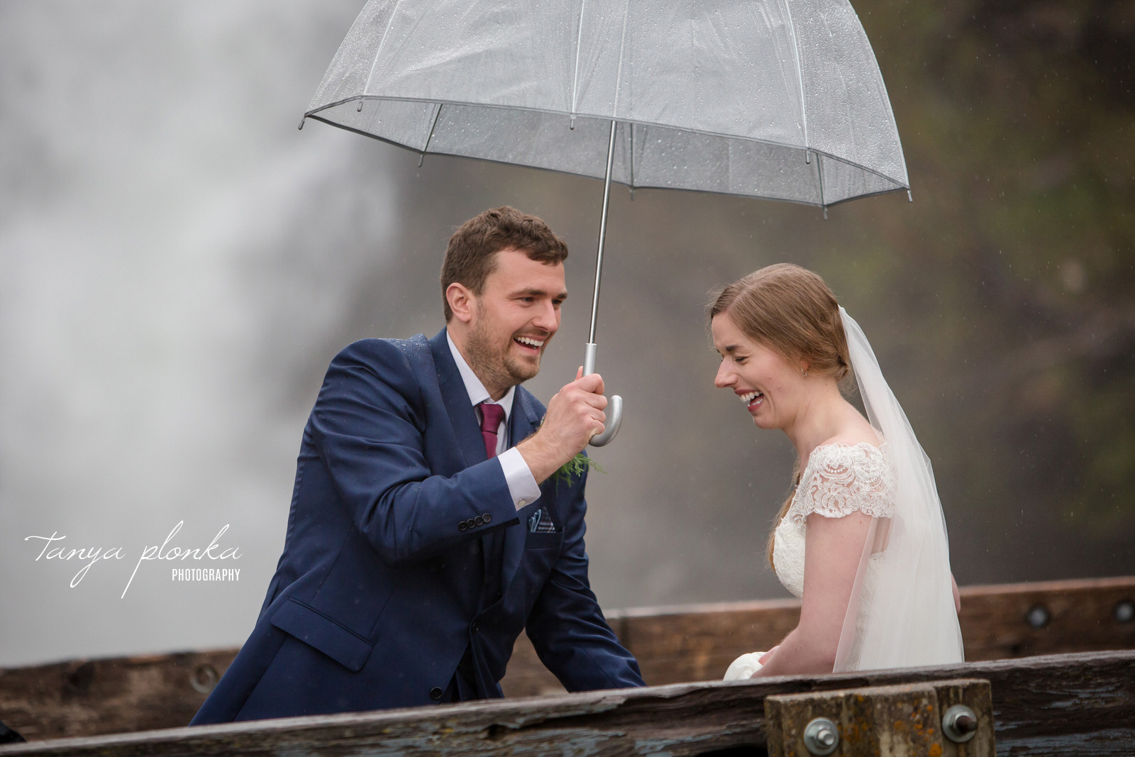 Groom holds umbrella over laughing bride
