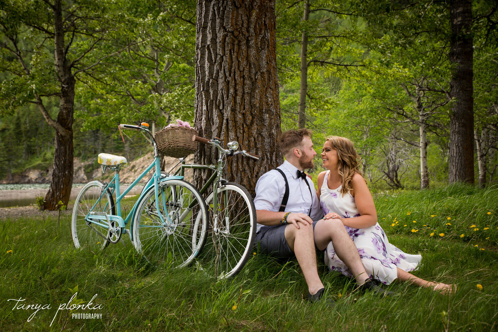 couple sit in grass laughing while their two vintage bicycles lean against a tree in Waterton
