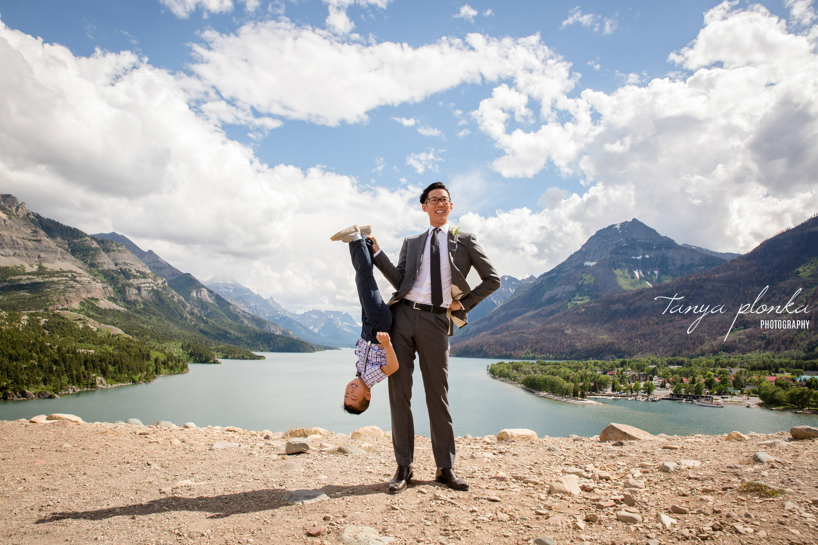 Groom standing in front of Waterton mountain view holds nephew upside down by the ankle