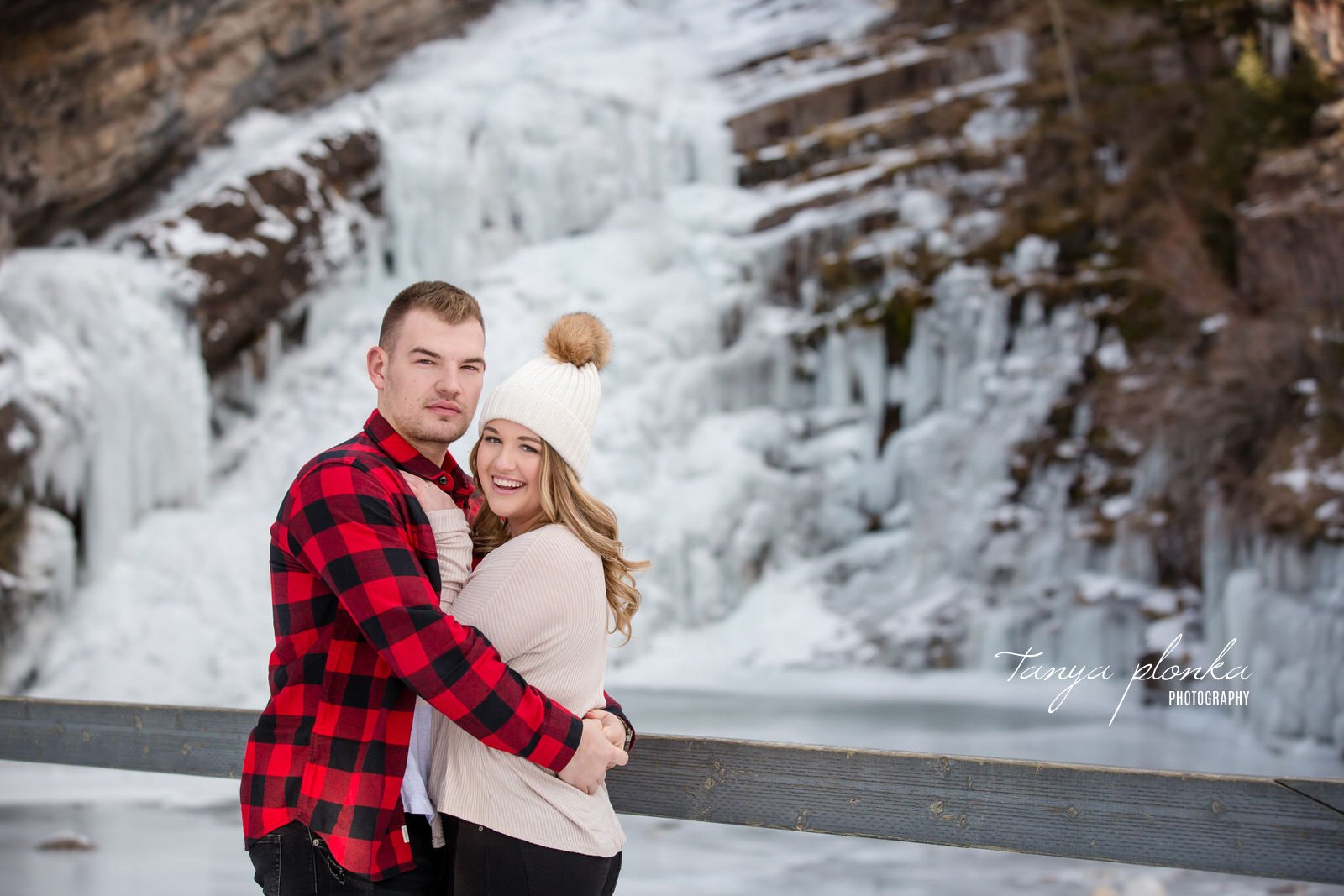 Man in red plaid shirt and woman in white toque hug in front of Cameron Falls in winter