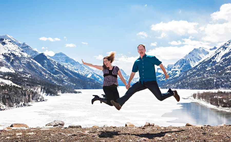 Waterton engagement photo in winter with couple jumping at cliff overlooking town