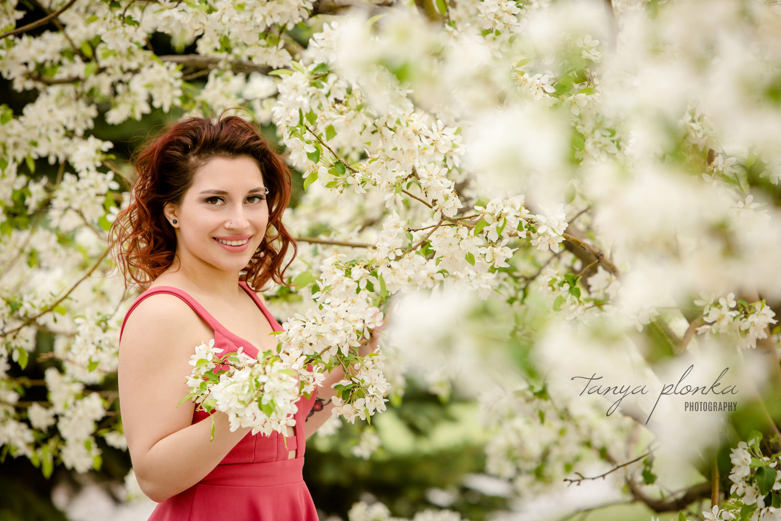 smiling woman in pink dress stands in white spring blossoms