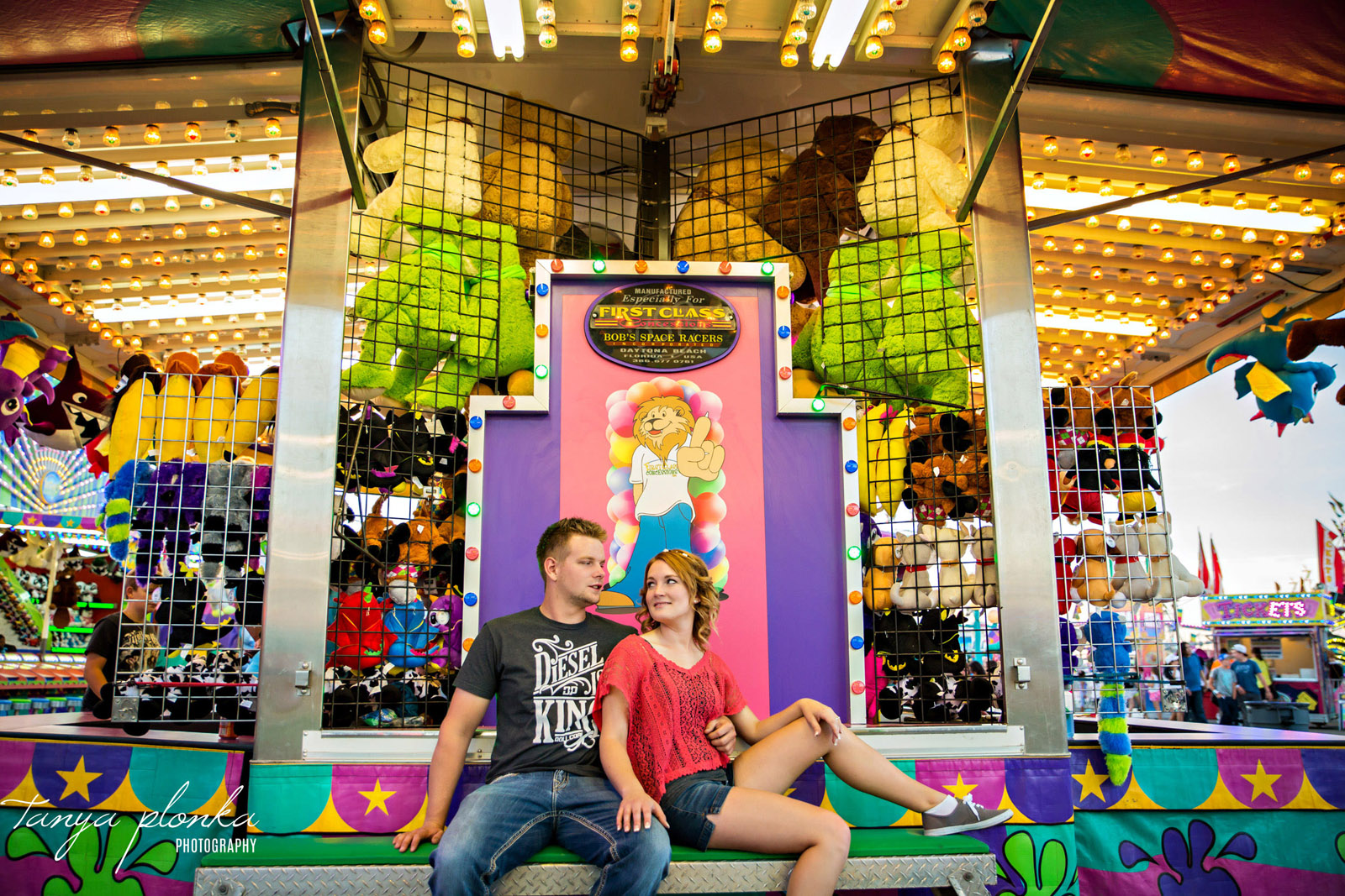 engaged couple sit together in front of fair games at Whoop Up Days