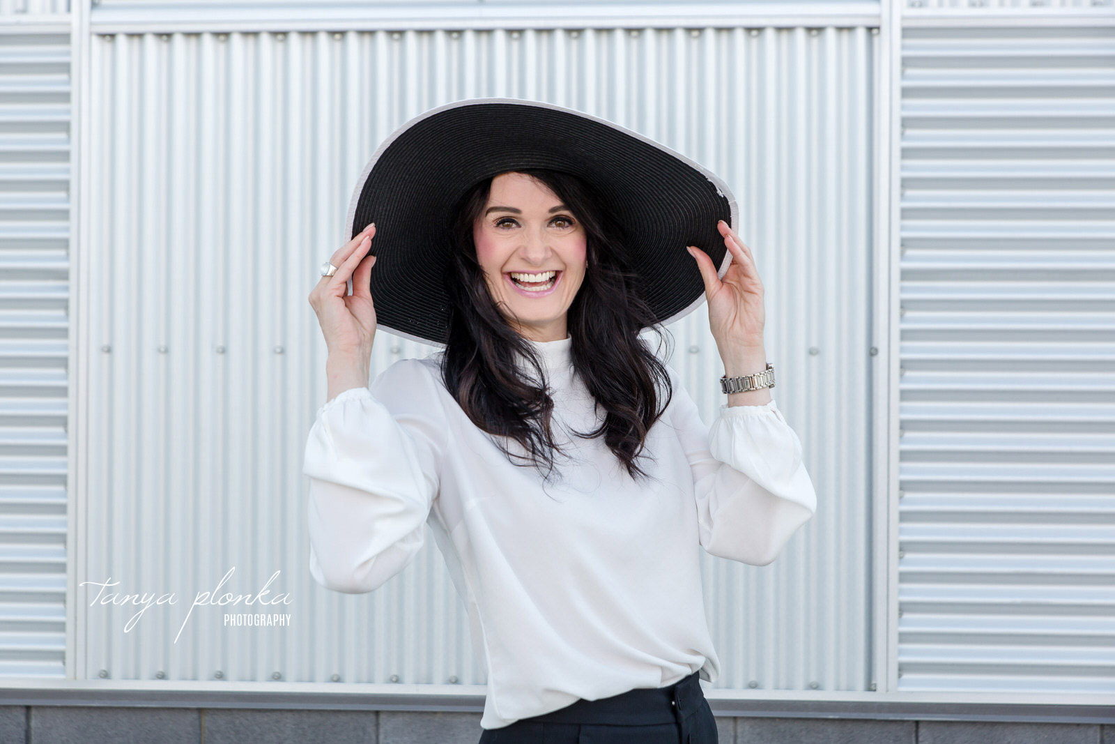 Woman in wide brimmed hat laughing